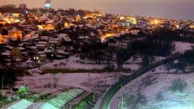 Cabañas cubiertas con nieve en la noche del invierno Foto de archivo libre de regalías