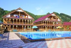 Cabañas de madera hermosas con la piscina en las montañas imagenes de archivo