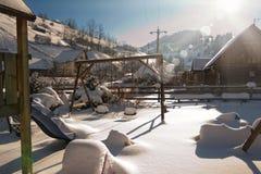 Cabañas de madera viejas y oscilaciones de madera del rumano cubiertos por la nieve Día de invierno frío en el campo Montañas cár Fotografía de archivo libre de regalías