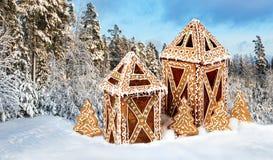 Cabañas del pan de jengibre en paisaje nevoso del invierno Foto de archivo libre de regalías