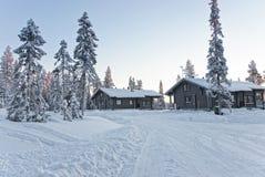 Cabañas en un bosque nevado en la puesta del sol en el pueblo de Ruka en F Foto de archivo