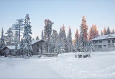 Cabañas en un bosque nevado en salida del sol en el pueblo de Ruka Foto de archivo