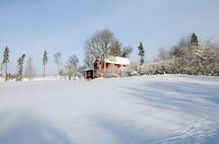 Cabañas rojas en invierno imagenes de archivo