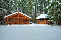 Cabaña de madera en bosque nevoso Imagen de archivo