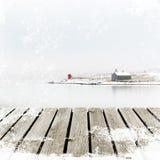 Cabaña de Noruega en costa del invierno con el muelle de madera de la plataforma con el grunge blanco de la nieve Imagen de archivo