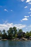 Cabaña roja sueca en una pequeña isla Imagen de archivo