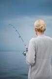 Caballa de la pesca de la mujer joven en vacaciones Fotografía de archivo libre de regalías