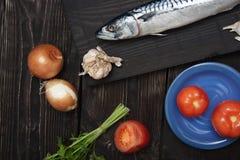 Caballa y verduras en una tabla de madera Imagen de archivo libre de regalías