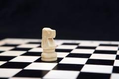 Caballero blanco y tablero de ajedrez en un fondo negro Fotografía de archivo libre de regalías