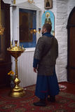Caballero en vestido medieval del correo en cadena y rogación en iglesia antes de un icono Fotos de archivo libres de regalías