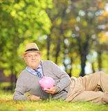 Caballero maduro satisfecho en un parque que sostiene una hucha Fotos de archivo