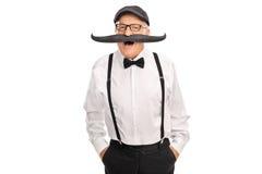 Caballero mayor alegre con un bigote falso Fotos de archivo libres de regalías