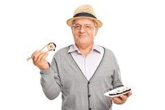 Caballero mayor alegre que lleva a cabo un pedazo de sushi Fotografía de archivo