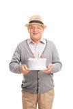 Caballero mayor alegre que sostiene una torta de cumpleaños Imágenes de archivo libres de regalías