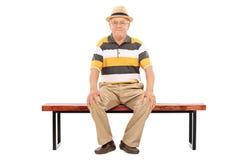 Caballero mayor casual que se sienta en un banco de madera Imágenes de archivo libres de regalías