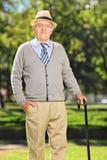 Caballero mayor despreocupado con un bastón que presenta en parque Fotografía de archivo libre de regalías