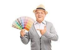 Caballero mayor que lleva a cabo una guía de la paleta de colores Foto de archivo libre de regalías