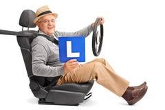 Caballero mayor que lleva a cabo una L-muestra Imágenes de archivo libres de regalías