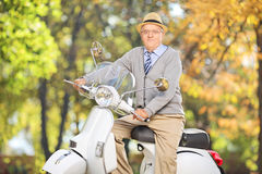 Caballero mayor que presenta en la vespa en un parque Fotos de archivo