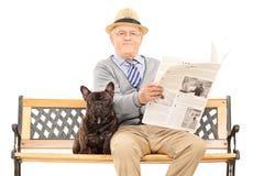 Caballero mayor que se sienta con su perro y que lee el periódico Foto de archivo libre de regalías
