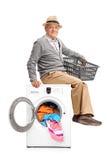 Caballero mayor que se sienta en una lavadora Foto de archivo libre de regalías