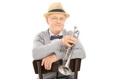 Caballero mayor que sostiene la trompeta asentada en silla Imagenes de archivo