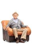 Caballero mayor relajado que se sienta en una butaca Imagen de archivo libre de regalías