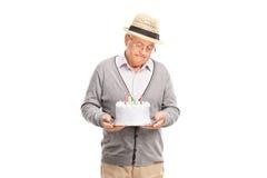 Caballero mayor solo que sostiene una torta de cumpleaños Foto de archivo