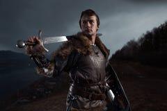 Caballero medieval con la espada en armadura como juego del estilo de tronos adentro fotografía de archivo