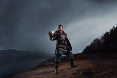 Caballero medieval con la espada en armadura como juego del estilo de tronos adentro imagen de archivo libre de regalías