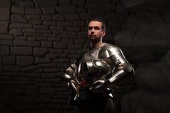 Caballero medieval que presenta con la espada en una piedra oscura Imagenes de archivo