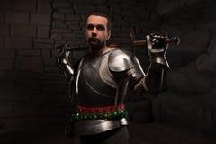 Caballero medieval que presenta con la espada en una piedra oscura Fotografía de archivo libre de regalías