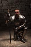 Caballero medieval que se arrodilla con la espada Imagen de archivo libre de regalías