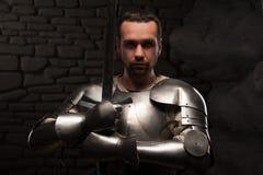Caballero medieval que se arrodilla con la espada Fotografía de archivo