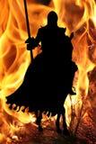 Caballero negro en un caballo en un fondo de la llama Imagenes de archivo