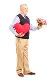 Caballero que sostiene un corazón rojo y las flores Foto de archivo