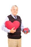 Caballero que sostiene un objeto y un regalo en forma de corazón Foto de archivo libre de regalías
