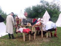 Caballeros de la gente en los trajes medievales que descansan sobre la tierra cerca de las tiendas antes de la batalla de los Vik imágenes de archivo libres de regalías