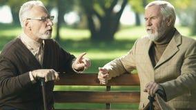 Caballeros jubilados que hablan en parque, intentando recordar, debilitación de envejecimiento de la memoria almacen de metraje de vídeo