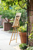 Caballete con la muestra o pintura delante del edificio de ladrillo al lado de la planta en conserva en jardín imagenes de archivo