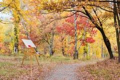 Caballete de madera con la lona vacía en bosque del otoño Fotos de archivo libres de regalías