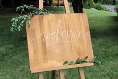 Caballete de madera con un tablero En el tablero escrito la pintura blanca - recepción Imágenes de archivo libres de regalías