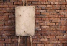 Caballete en blanco del grunge en una pared de ladrillo Imagen de archivo libre de regalías