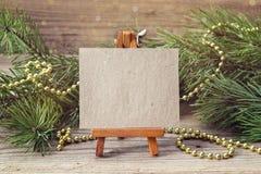 Caballete miniatura con la tarjeta en blanco, las ramas y la Navidad diciembre del pino Imagenes de archivo