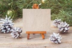 Caballete miniatura con la tarjeta en blanco, las ramas y la Navidad diciembre del pino Fotos de archivo libres de regalías