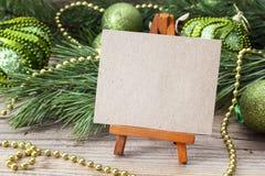 Caballete miniatura con la tarjeta en blanco, las ramas y la Navidad diciembre del pino Imágenes de archivo libres de regalías