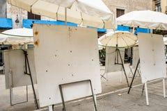 Caballetes blancos del metal sucio vacío en la calle debajo de los paraguas blancos Van a los artistas de la calle para el fin de imagen de archivo