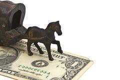 Caballo de hierro y banco de dólares en el fondo blanco Imagen de archivo libre de regalías