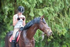 Caballo de la castaña con el adolescente con el smartphone que se sienta en él Fotografía de archivo