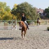 Caballo de montar a caballo de la chica joven en la competencia ecuestre Imagen de archivo